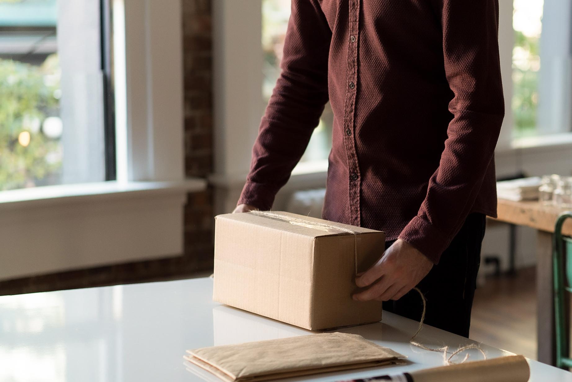 A man preparing a box for return - Trustly E-commerce
