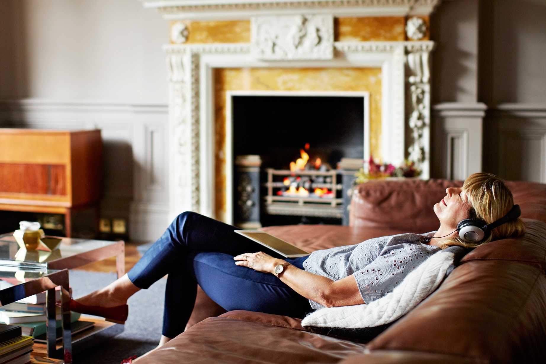 A woman listening to music on her tablet in a living room - Trustly Direct Debit